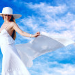 Young beautiful women in the white with pareo on the blue sky ba - Stock Photo