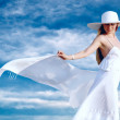 Stock Photo: Young beautiful women in the white with pareo on the blue sky ba
