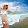 Young beautiful women in the white on the sunny tropical beach - Stock Photo