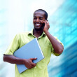 Young happy black man or student with laptop on the business bac — ストック写真