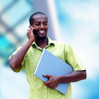 Young happy black man or student with laptop on the business bac - Stock Photo