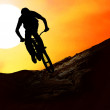 Silhouette of a man on muontain-bike, sunset - Photo