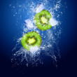 Foto Stock: Water drops around kiwi and ice on blue background