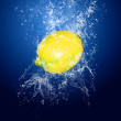 Water drops around lemon on blue background — Stock Photo