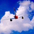 Airplane at fly on the sky with clouds — Lizenzfreies Foto