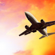 Stock Photo: Airplane on sunset sky