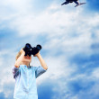 Young boy watch in the field-glass under sky - Stock Photo
