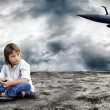 Young boy seating with notebook on the land and military plane - Stock Photo