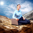 Happy Businesswoman seating with laptop on the mountain under bl - Stock Photo