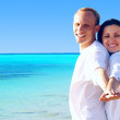 Stock Photo: View of happy young couple walking on the beach, holding hands.