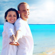 View of happy young couple walking on the beach, holding hands. — Stock Photo #6354663