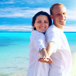 View of happy young couple walking on the beach, holding hands. — Stock Photo #6354667