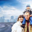 Happy family portrait outdoors smiling on the road in city — Stock Photo