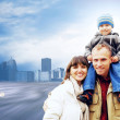 Happy family portrait outdoors smiling on the road in city — Stock Photo #6354714