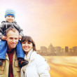 Happy family portrait outdoors smiling on the road in city — Stock Photo #6354715