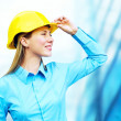 Young architect-woman wearing a protective helmet standing on th — Stock Photo