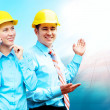 Young architects wearing a protective helmet standing on the bui — Stock Photo #6355032