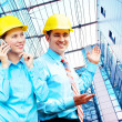 Young architects wearing a protective helmet standing on the bui — Stock Photo #6355038