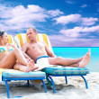 Rear view of a couple on a deck chair relaxing on the beach — Stockfoto
