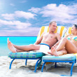 Rear view of a couple on a deck chair relaxing on the beach — Stock Photo #6355050
