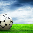 Soccer ball on green grass and sky background - Stock fotografie