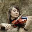 Beautiful female violinist playing violin on the grunge backgrou — ストック写真