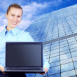 Happiness businesswoman with laptop on blur business architectur - Photo