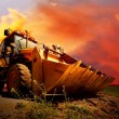 Stock fotografie: Yellow tractor on golden surise sky