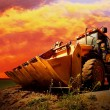 Yellow tractor on golden surise sky - ストック写真