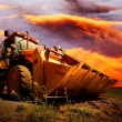 Foto Stock: Yellow tractor on golden surise sky
