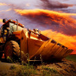 Yellow tractor on golden surise sky - Stok fotoğraf