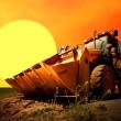 Yellow tractor on golden surise sky — Stock Photo