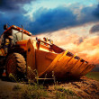 Yellow tractor on golden surise sky - Stock Photo