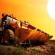 Yellow tractor on golden surise sky — Stock Photo