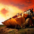 Stock Photo: Yellow tractor on golden surise sky