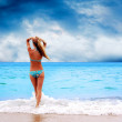 Foto Stock: Young beautiful women on sunny tropical beach in bikini