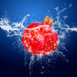 Water drops around red fruit on blue background — Foto Stock