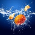 Water drops around mandarin on blue background — Stock Photo