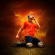 Royalty-Free Stock Photo: Football player in fires flame on the outdoors field