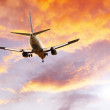 Airplane on sunset sky — Stockfoto