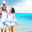 View of happy young family having fun on the beach - Foto de Stock  