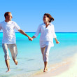 View of happy young couple walking on the beach, holding hands. — Stock Photo #6356320