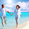 View of happy young couple walking on the beach, holding hands. — Stock Photo #6356322