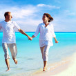 View of happy young couple walking on the beach, holding hands. — Stock Photo #6356326