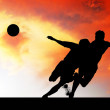 Silhouettes of footballers on the sunset sky - Lizenzfreies Foto