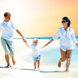 View of happy young family having fun on the beach — Stock Photo #6356367