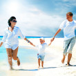 Stock Photo: View of happy young family having fun on the beach