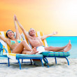 Rear view of a couple on a deck chair relaxing on the beach — Stock Photo #6356528