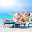 Rear view of a couple on a deck chair relaxing on the beach — Stock Photo #6356531
