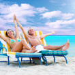 Rear view of a couple on a deck chair relaxing on the beach — Stock Photo #6356534